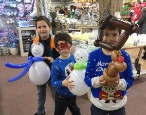 Children holding Christmas balloon models.