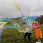 Giant bubble entertainers making large bubbles at an event in South Cerney.