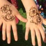 Henna tattoos for children at festival wedding party in Bristol.