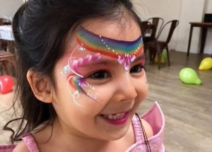 Rainbow princess face painting painted at a party in Cirencester.