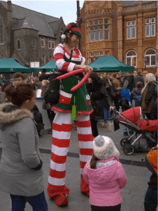 Lucy elf balloon modeller on stilts at a Christmas event in Bristol.