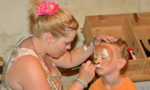 Cheryl face painting a child as a lion.