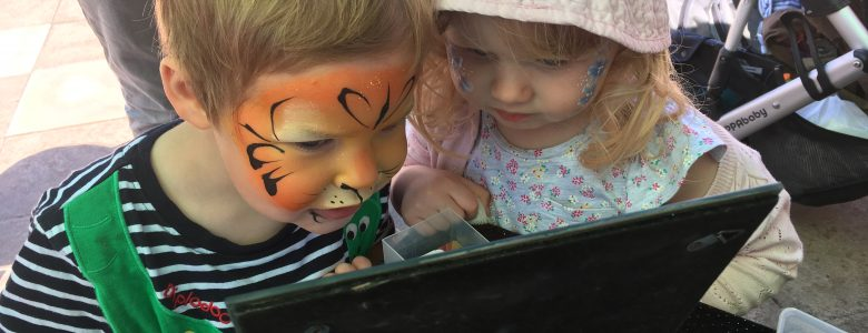 Children with their face painted looking in a mirror.