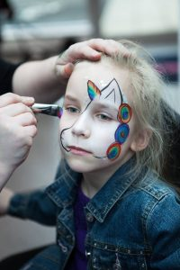 Face painting a unicorn.