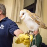 Gary holding an owl speaking to a class room.