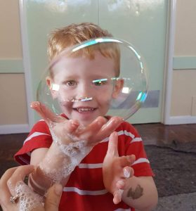 Child holding a bubble at a senco school activity.