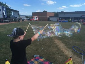 Child making a giant bubble at an event in Swindon, kids entertainer.