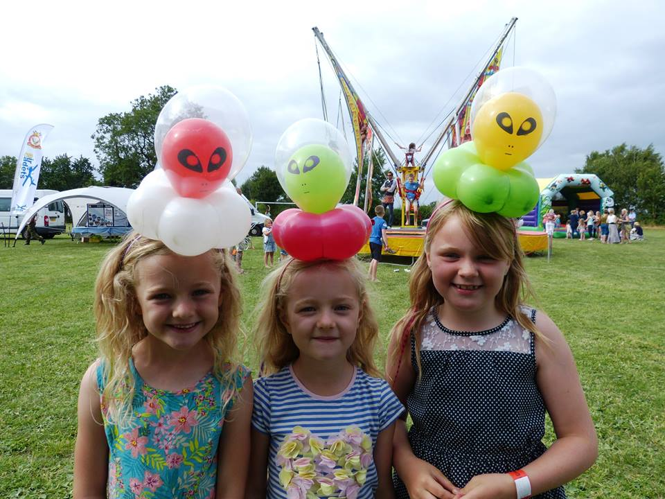 Children wearing alien balloon model head bands at event in Bristol.
