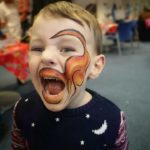 Boy with his face painted as a orange dinosaur at a party in Cheltenham.