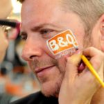 Corporate event face painting, B&Q logo face painting at an in-store event in Wales.
