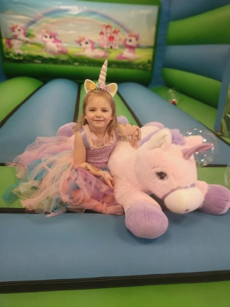 Unicorn party with themed bouncy castle and pony rides.